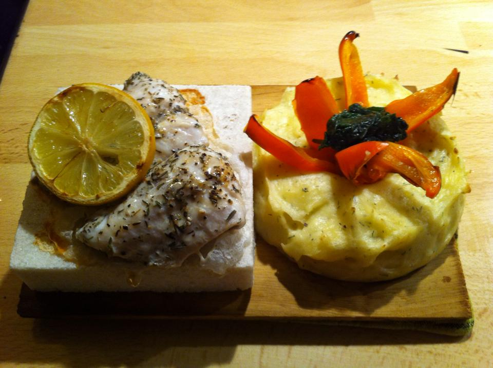 Salt Stone baked bass with thyme and mashed potatoes on wooden board